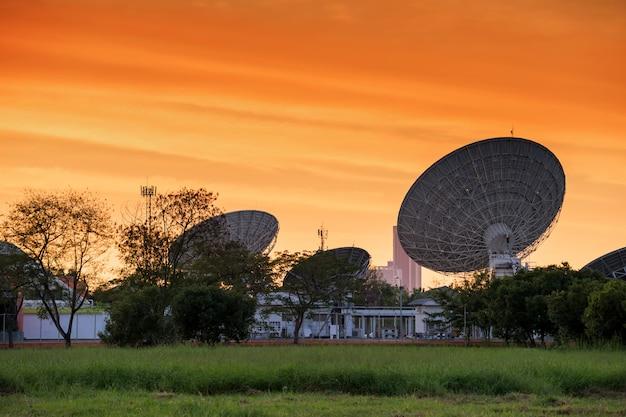 Grandi piatti satelitari con cielo crepuscolare