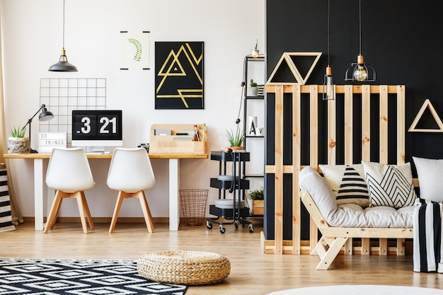 Grande scrivania scandi, sedie di design, computer, poster e rack in camera moderna e accogliente per un adolescente con interni in bianco e nero e decorazioni in pallet di legno nella zona giorno con divano