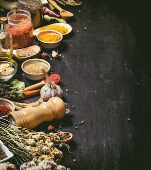 Grande insieme di spezie ed erbe indiane sulla lavagna nera