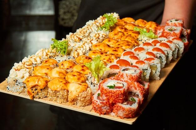 Grande set di rotoli di sushi su una tavola nelle mani di un cameriere