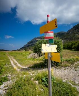 Grande cartello con diverse direzioni in piedi all'inizio del percorso turistico