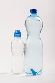 Bottiglie d'acqua grandi e piccole di plastica