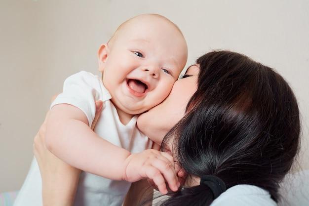 Grande sorriso mamma bambino che abbraccia bambino bambino ridendo tra le braccia della madre ridendo molto il concetto di una famiglia felice Foto Premium