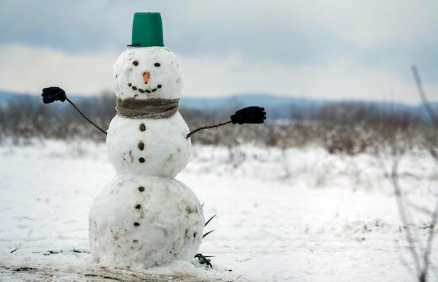 Grande pupazzo di neve sorridente con cappello a secchiello, sciarpa e guanti sul paesaggio invernale campo innevato bianco, alberi neri sfocati e sfondo spazio copia cielo blu . buon natale e felice anno nuovo biglietto di auguri.