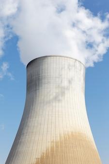 Grande ciminiera della fabbrica nucleare con cielo blu