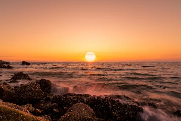 Grande sole sullo skyline al tramonto. spruzzata dell'acqua dell'oceano sulla spiaggia della roccia con il bello cielo di tramonto e le nuvole arancio. onda del mare che spruzza sulla pietra in riva al mare in estate. paesaggio naturale. paesaggio marino tropicale.