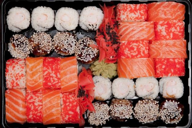 Grande set di sushi ib scatola di plastica nera su sfondo bianco, vista dall'alto vicino, copia dello spazio
