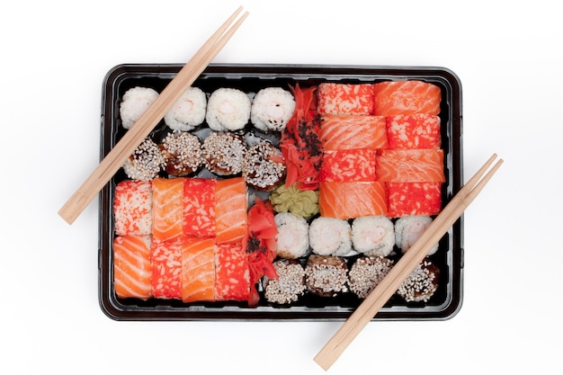 Grande set di sushi ib scatola di plastica nera su sfondo bianco, vista dall'alto vicino, copia dello spazio.