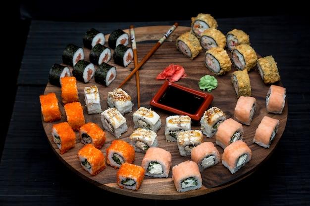 Grande set sushi con involtini california, filadelfia, unagi e dragon. cibo giapponese con posto per la ricetta.