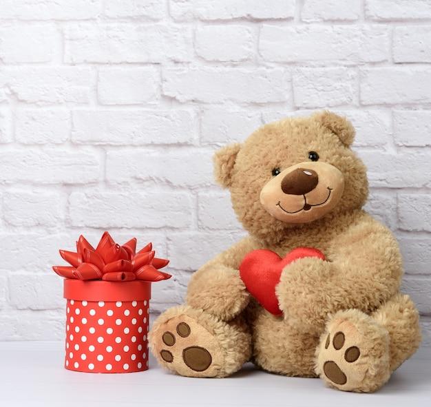 Grande orsacchiotto e scatola di cartone con fiocco rosso su sfondo bianco muro di mattoni