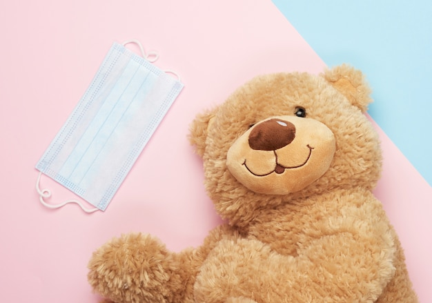 Grande orsacchiotto e maschere mediche su una superficie blu e rosa