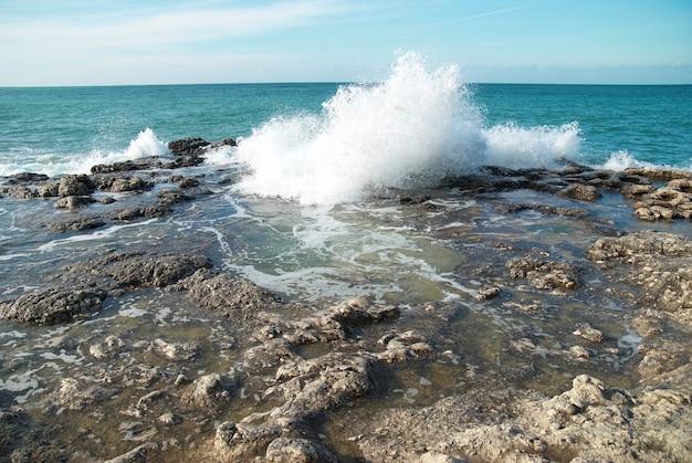 Grandi onde che si infrangono sulla riva con schiuma di mare
