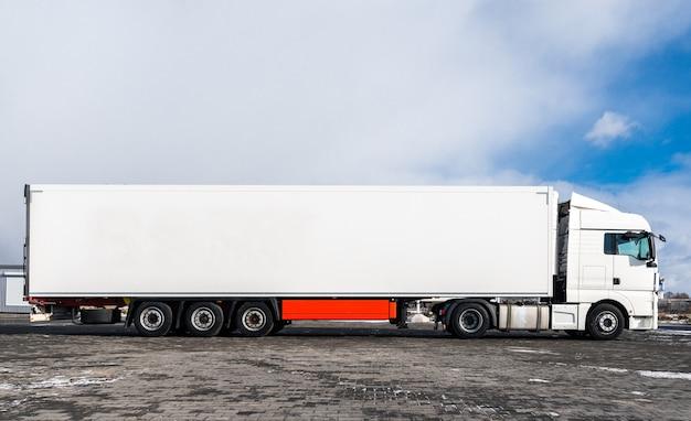 Un grosso camion bianco con un rimorchio bianco in piedi sulla strada di campagna contro un cielo blu con nuvole. concetto di trasporto