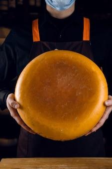 Grande forma di formaggio giallo nelle mani. venditore in maschera per protezione contro il coronavirus covid-19. tenendo il formaggio rotondo.