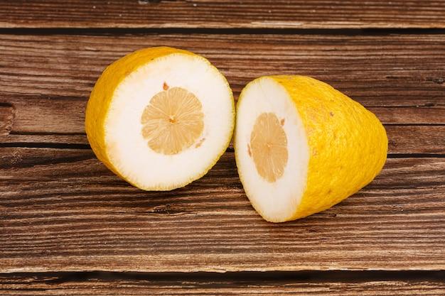 Grande limone giallo sul tagliere su un tavolo di legno