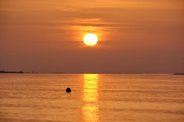 Grande sole giallo che tramonta sulla superficie del mare.
