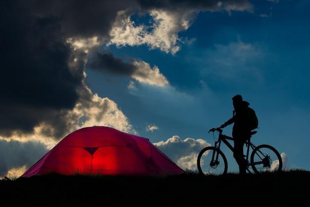 Avventura in bici in campagna. siluetta della persona con una bicicletta vicino alla tenda.