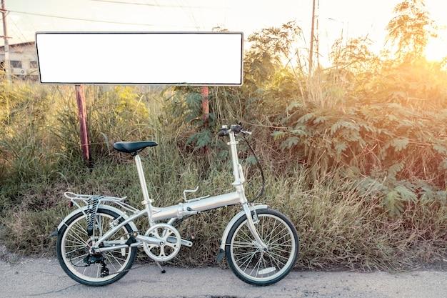 Pieghevole bici parcheggiata sul prato con poster bianco splendente