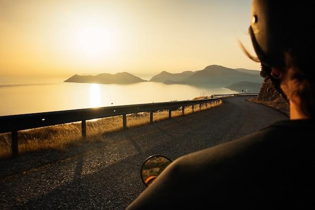 Motociclista alla guida di una moto lungo la strada tortuosa di montagna con splendida vista sul mare e sul tramonto