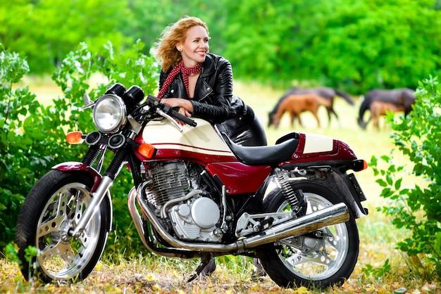 Ragazza motociclista in una giacca di pelle su una moto sullo sfondo dei cavalli