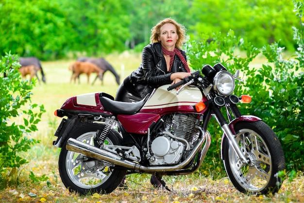 Ragazza motociclista in una giacca di pelle su una moto sullo sfondo dei cavalli.