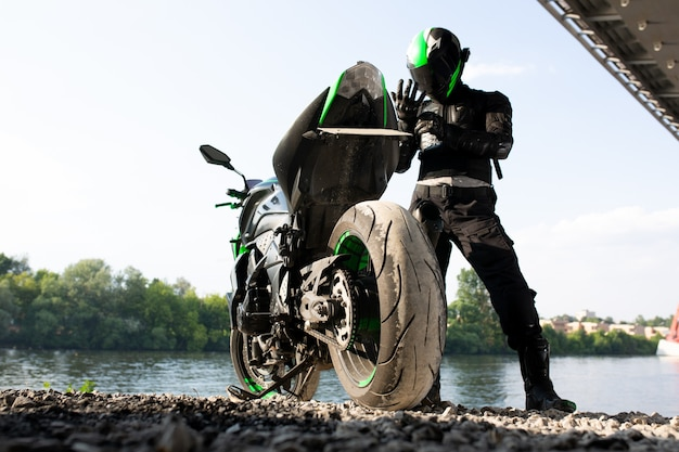 Uomo motociclista e motocicletta con sfondo fluviale, viaggio in moto rider sulla strada in riva al fiume, godendo della libertà e dello stile di vita attivo. concetto di touring di viaggio enduro