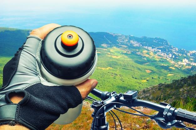 Motociclista in montagna che beve dalla bottiglia d'acqua