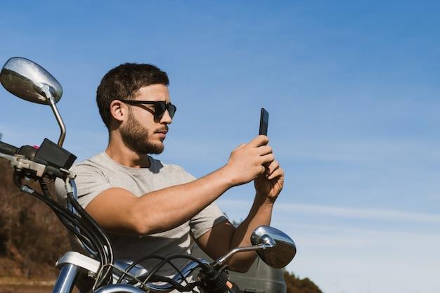 Motociclista seduto sulla moto che scatta una foto del paesaggio con il cellulare