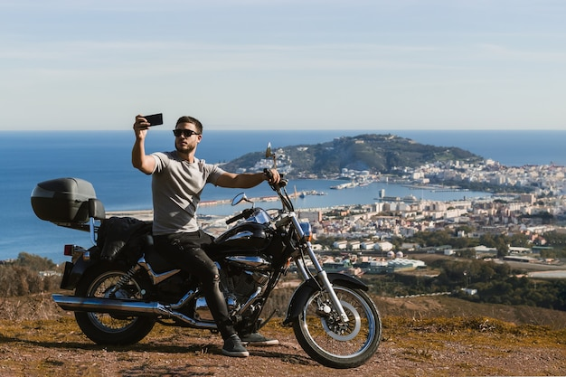 Motociclista seduto sulla moto prendendo selfie con il paesaggio con il cellulare