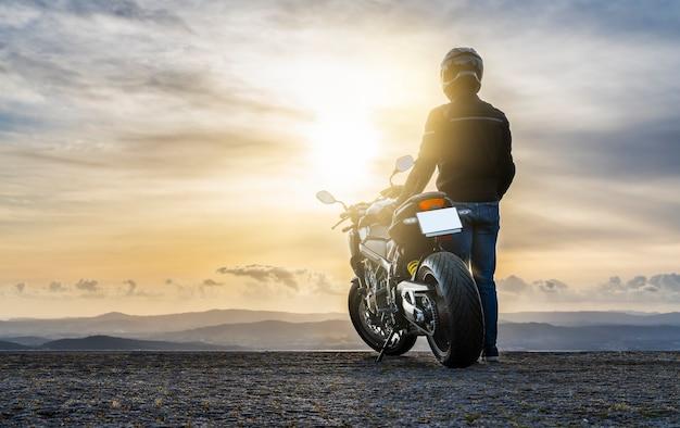 Motociclista in piedi accanto alla moto, guardando il tramonto - copia spazio.