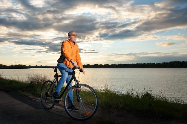 Il motociclista si è fermato sullo sfondo del sole al tramonto sul lago