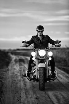 Motociclista con casco, occhiali da sole e giacca di pelle in sella alla sua moto su strada.