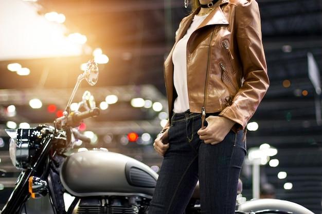 Donna del motociclista in una giacca di pelle marrone con una moto su sfondo di strada