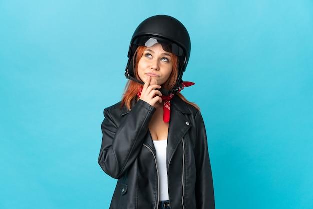 Donna motociclista isolata sull'azzurro che ha dubbi mentre cerca