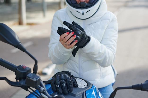 Donna del motociclista che toglie i suoi guanti