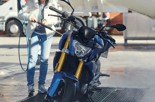 Donna del motociclista che lava la sua moto