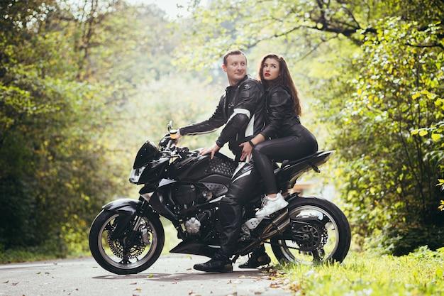 Motociclisti in vestiti di pelle, uomo e donna, seduti su una moto sportiva nera nel bosco