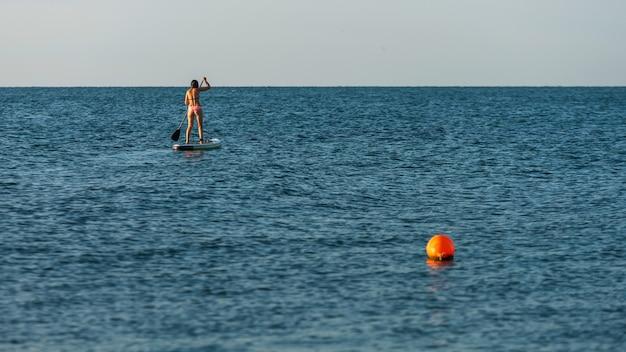 Ragazza bikini si alza in piedi sup paddleboarding sull'acqua blu del mare