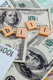 Iscrizione di fattura su cubi di legno sulla trama di dollari americani e banconote in euro