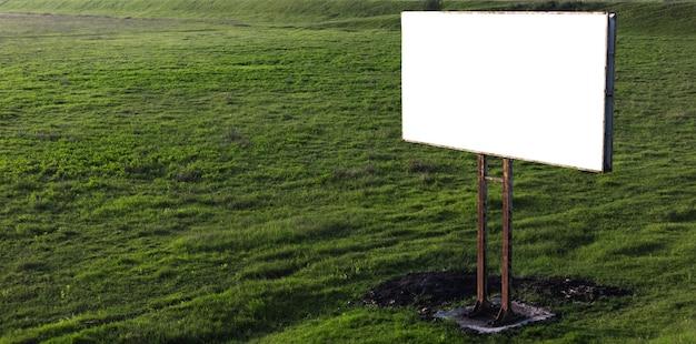 Tabellone per le affissioni in bianco per poster pubblicitario all'aperto nel campo verde