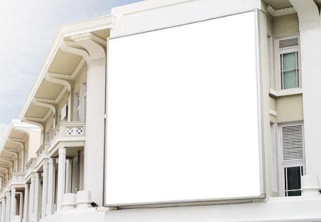 Tabellone per le affissioni sull'edificio con un bel sole e un cielo luminoso mockup di un segnaposto banner