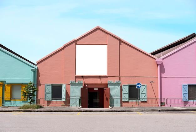 Tabellone per le affissioni su edifici colorati vicino al ciglio della strada con un modello di strada chiara di un segnaposto banner