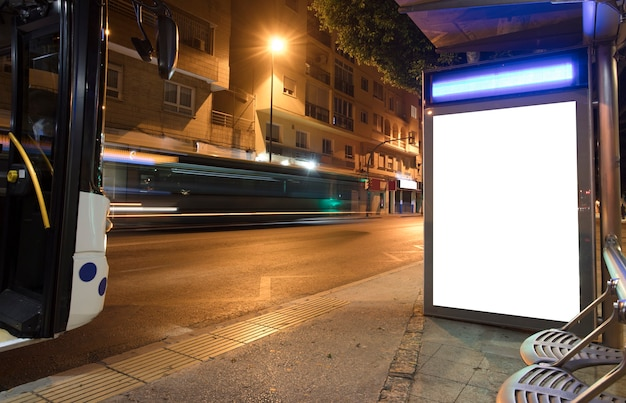 Cartellone luminoso in centro città di notte con 2 autobus in movimento