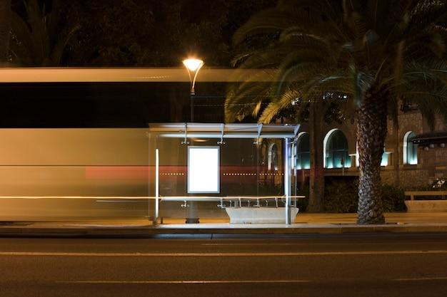 Tabellone per le affissioni con luce nel centro della città di notte con autobus in movimento