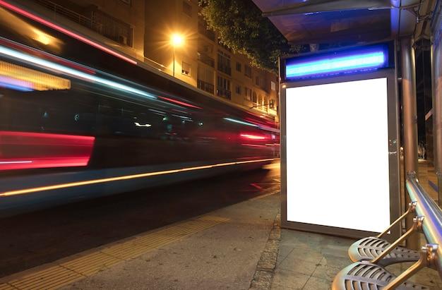 Cartellone luminoso in centro città di notte con bus