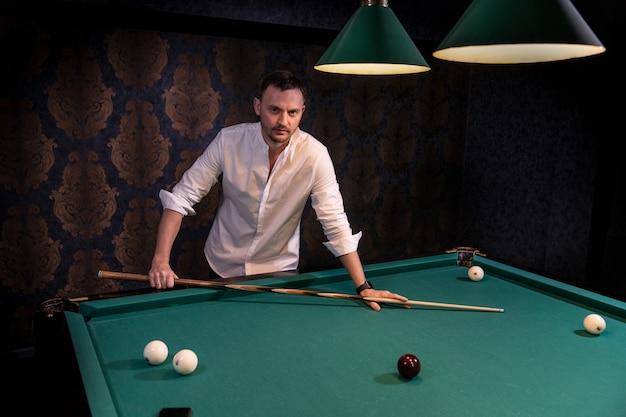 Il giocatore di biliardo sta al tavolo tenendo una stecca di legno
