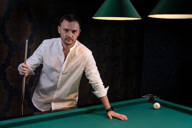 Il giocatore di biliardo sta al tavolo con una mano appoggiata al panno verde e con l'altra tiene una stecca di legno