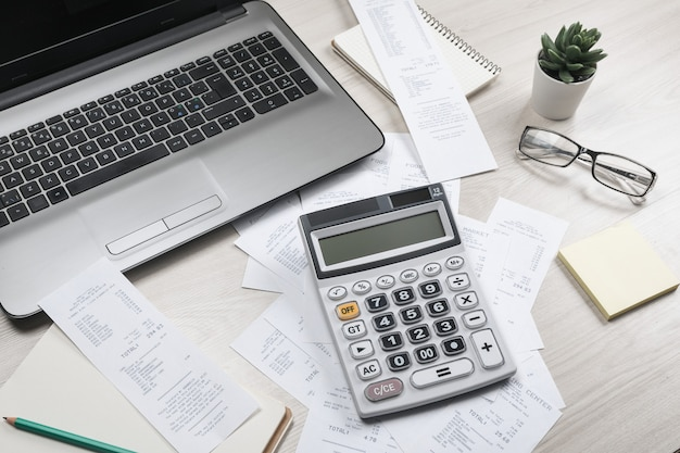 Fatture e calcolatrice con assegni. calcolatrice per calcolare le bollette al tavolo in ufficio. calcolo dei costi.
