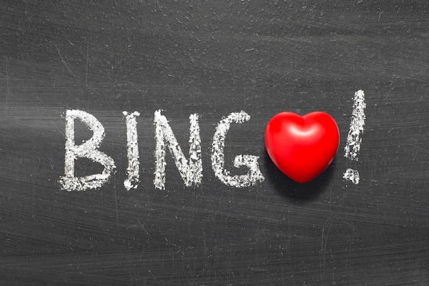Parola di bingo scritta a mano sulla lavagna con il simbolo del cuore invece di o