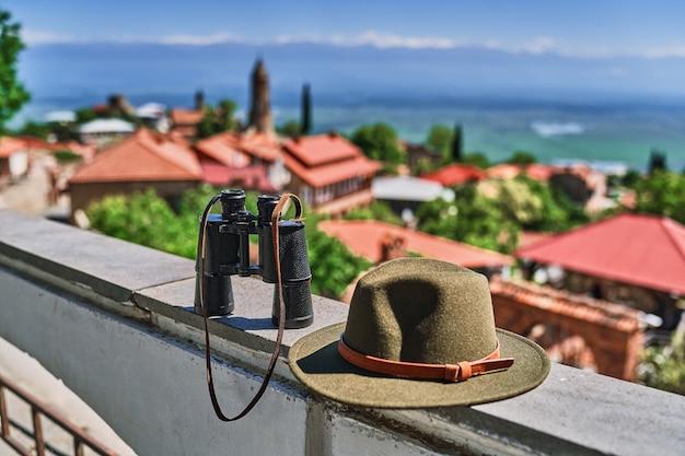 Binocolo e cappello di feltro sul punto di vista sullo sfondo delle case di tegole rosse a sighnaghi città dell'amore, regione di kakheti, paese della georgia
